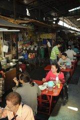 Asiaten essen an den Tischen bei den Garkuechen in einem Markt / Bangkok / T