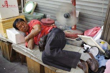 Schlafender Mann laesst sich von einem Ventilator den Ruecken kuehlen / Bangko