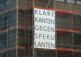 Protestplakat gegen Spekulation mit Immobilien an einem Baugeruest