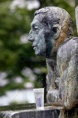 Berlin  Becher mit Wasser vor einer Brunnenfigur
