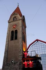 Alter Kirchturm mit modernem Anbau und leuchtenden Weihnachtsmaennern