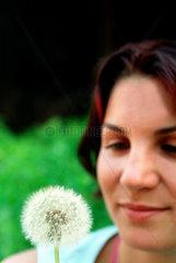 Berlin  eine junge Frau mit Pusteblume