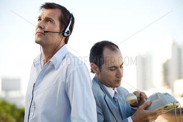Two men standing back to back  one using headset  the other holding landline phone