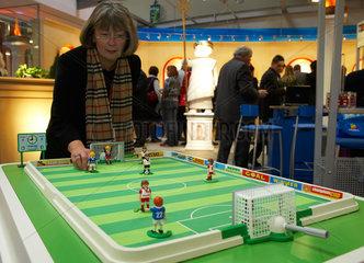 Eine Messebesucherin testet Spielfiguren von Playmobil fuer Tischfussball