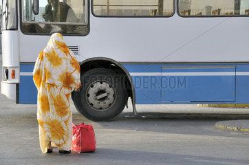 Marokkanerin wartet auf Bus in Marokko