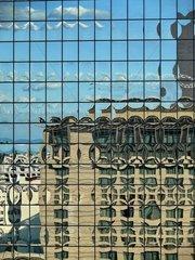 Gebaeude spiegeln sich in einer Glasfassade