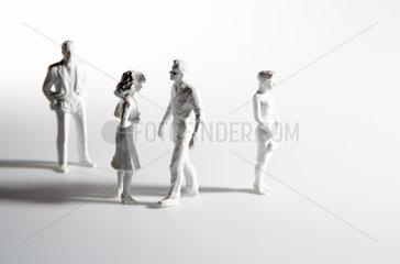 Vier Miniaturfiguren mit Schlagschatten vor weissem Hintergrund