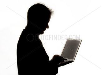 Silhouette eines Mannes mit einem Laptop in der Hand