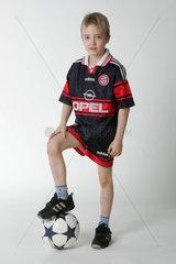 Junge posiert mit einem Fussball