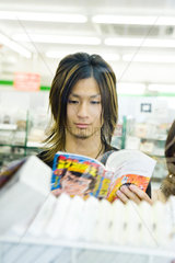 Young Japanese man reading comic book in store