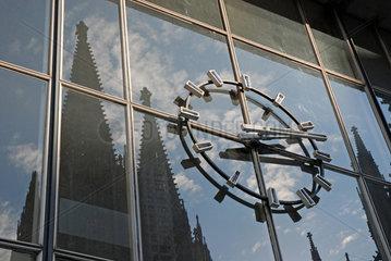 Spiegelung des Koelner Dom in der Glasfassade des Hauptbahnhofs mit der Bahnhofsuhr