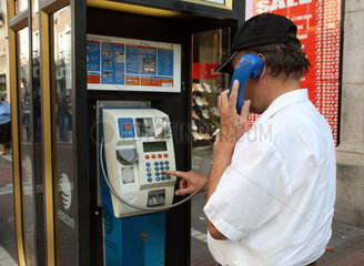 Dublin  ein Mann waehlt eine Telefonnummer an einem oeffentlichen Fernsprecher von Eircom