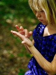 Maedchen betrachtet ihre Hand