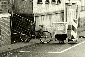 Fahrrad mit Anhaenger und einem Werbezettel fuer Winterdienst. Bicycle with a trailer and a promotional list for winter maintenance.
