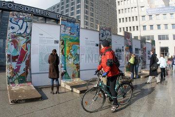 Berlin  Touristen informieren sich an einem Denkmal der Berliner Mauer