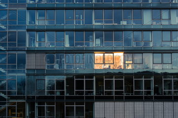 Einzelnes beleuchtetes Buero in einen Buerogebaeude mit Glasfassade