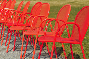 Rote Metallstuehle in einem Park