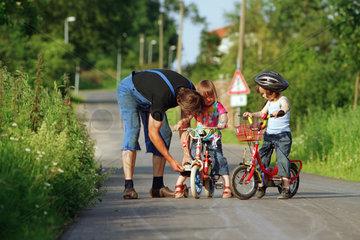 Mecklenburg  Strassenverkehr - Kinder mit Fahrraedern auf der Dorfstrasse