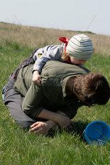 Mutter und Sohn  2 5 Jahre alt  toben ausgelassen auf einer Wiese (model released)