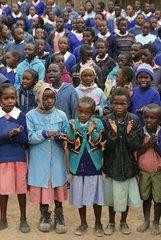 Afrikanische Schueler in Schuluniformen singen beim Morgenappell in einer Schule