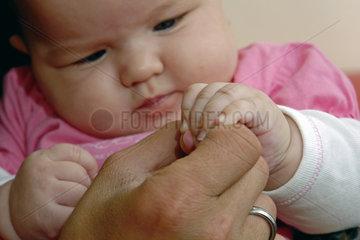 Baby greift die Hand seiner Mutter