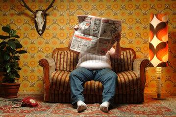 Ein dicker Mann sitzt auf der Couch und liest eine Zeitung