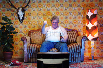 Dicker Mann sitzt auf der Couch und guckt Fernsehen