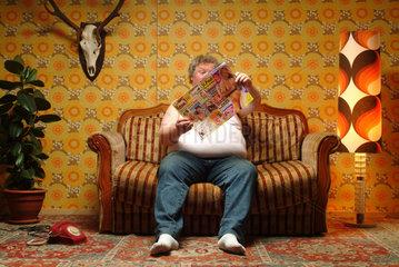 Ein dicker Mann mit Sexheftchen auf der Couch