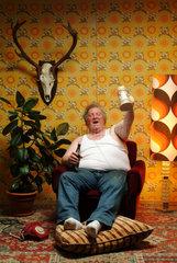 Dicker Mann sitzt entspannt im Sessel