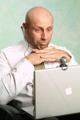Mann arbeitet an seinem Powerbook und schaut nachdenklich in die Webcam