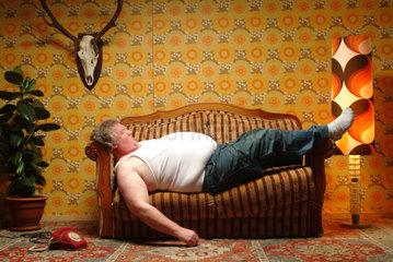 Dicker Mann in Unterhemd schlaeft auf der Couch