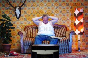 Ein dicker Mann sitzt auf der Couch und aergert sich