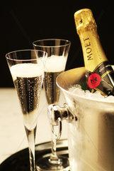 2 Champagnerglaeser stehen neben einem Kuehler mit einer Flasche MOET