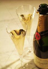 2 Champagnerglaeser stehen neben einer Flasche MOET