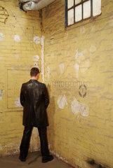 Mann uriniert in eine Hausecke