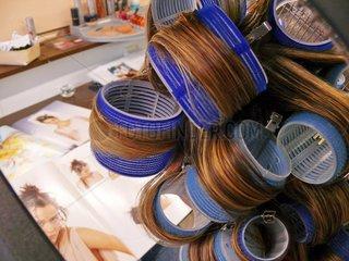 Junge Frau mit Lockenwicklern beim Friseur