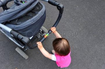 Kleines Maedchen schiebt einen Kinderwagen