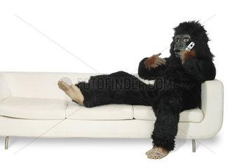 Mann in Gorillakostuem sitzt auf einer Couch und telefoniert
