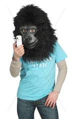 Mann mit Gorillakopf guckt auf sein Handy