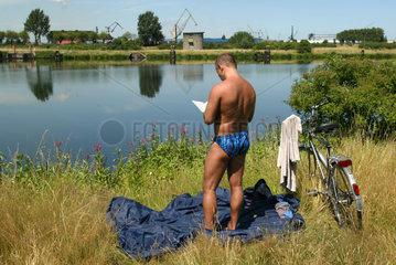 Mann steht in der Sonne an der Ruhr in Duisburg