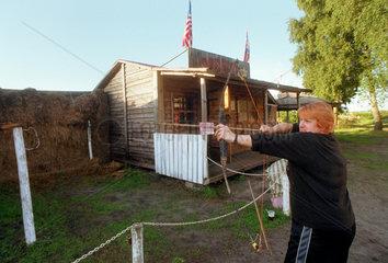 Frau schiesst Pfeil und Bogen im Wild-West-Dorf WESTERN CITY in Leba  Polen
