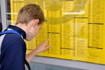 Alleinreisender Junge studiert Abfahrtszeiten der Z__ge