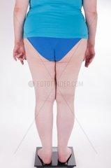 Eine dicke Frau seteht auf einer Waage