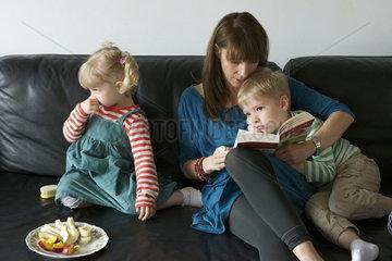 Mutter mit zwei Kindern auf dem Sofa