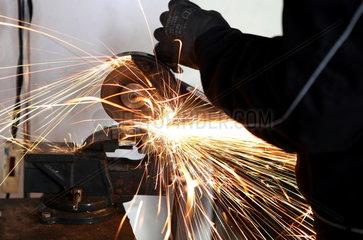 Kfz-Werkstatt: Ein Mechatroniker flext Metall