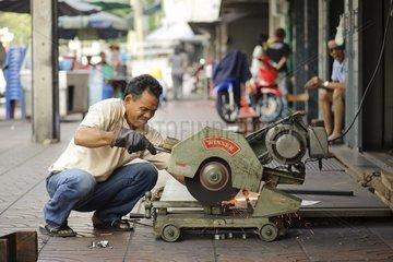 Asiate saegt Metallwinkel (Schlosser) / Bangkok / Thailand / SUEDOSTASIEN-RE