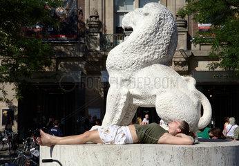 Amsterdam  Nationaal Monument  Frau liegt in der Sonne und hoert Musik