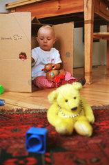 Kleinkind (11 Monate) spielt mit Pappkarton  Berlin