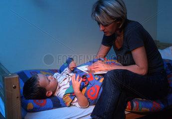 Familienalltag  Mutter bringt ihr Kind zu Bett
