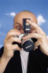 Hamburg  Deutschland  ein Mann haelt eine Kamera